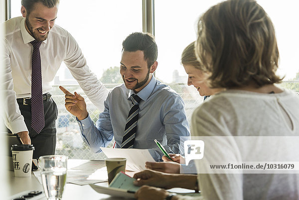 Lächelnde Geschäftsleute bei einer Besprechung im Konferenzraum