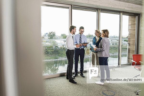 Geschäftsleute mit digitalem Tablett und Dokumenten im Gespräch am Fenster
