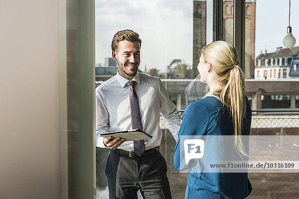 Lächelnde junge Geschäftsfrau und Geschäftsmann mit digitalem Tablett