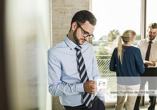 Geschäftsmann beim Blick auf Smartphone mit Kollegen im Hintergrund