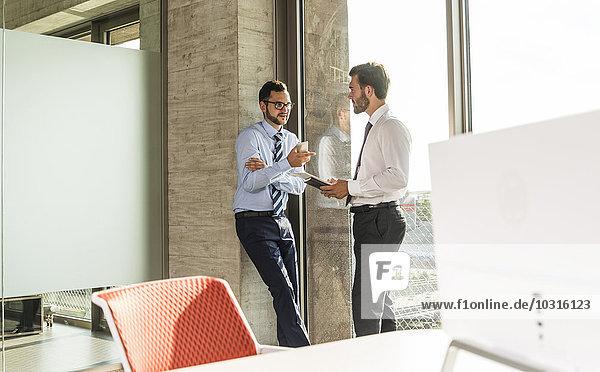 Zwei junge Geschäftsleute sprechen am Fenster im Büro