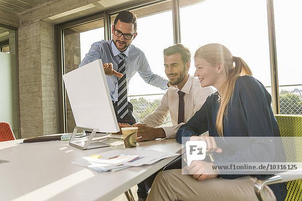 Drei junge Geschäftsleute im Konferenzraum mit Blick auf den Monitor