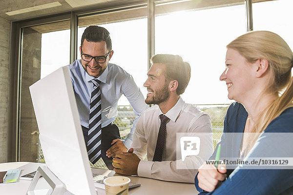 Drei glückliche junge Geschäftsleute im Konferenzraum mit Blick auf den Monitor