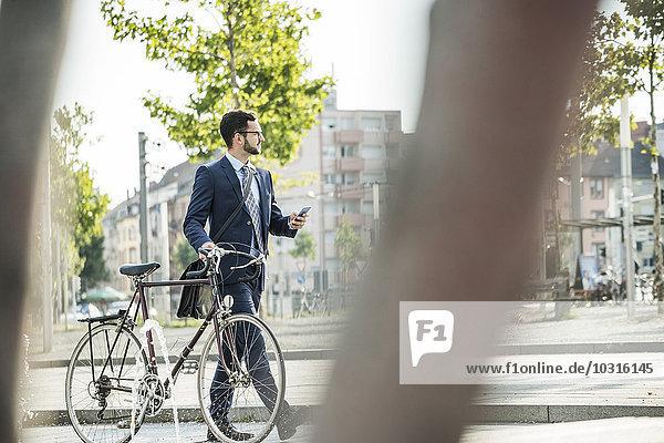 Junger Geschäftsmann schiebt Fahrrad  hält Smartphone