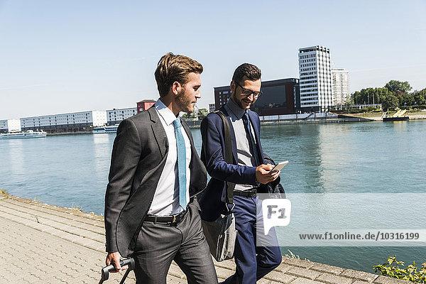 Zwei junge Geschäftsleute auf Geschäftsreise  die am Fluss spazieren gehen