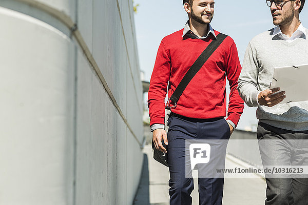 Two young businessmen walking in city carrying files