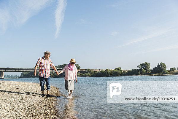 Germany  Ludwigshafen  happy senior couple walking hand in hand at riverside