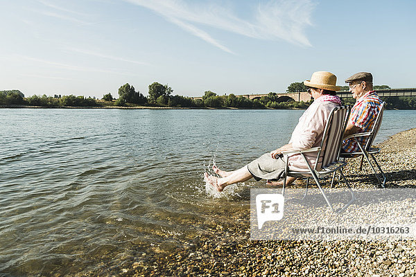 Germany  Ludwigshafen  senior couple sitting on folding chairs at riverside splashing with feet in water