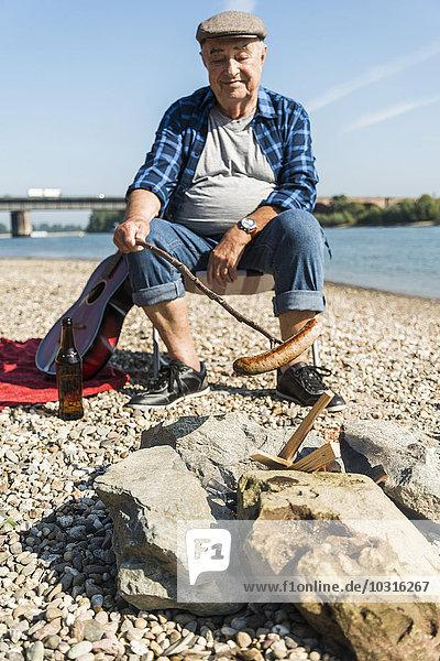 Deutschland  Ludwigshafen  Porträt eines lächelnden Senioren beim Grillen am Strand