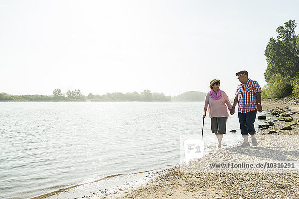 Germany  Ludwigshafen  senior couple walking hand in hand at riverside