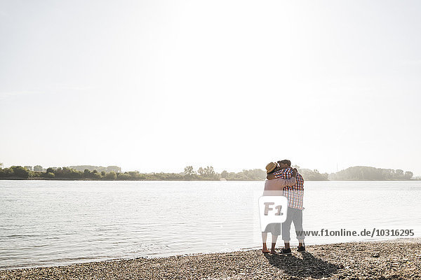 Germany  Ludwigshafen  kissing senior couple standing at riverside