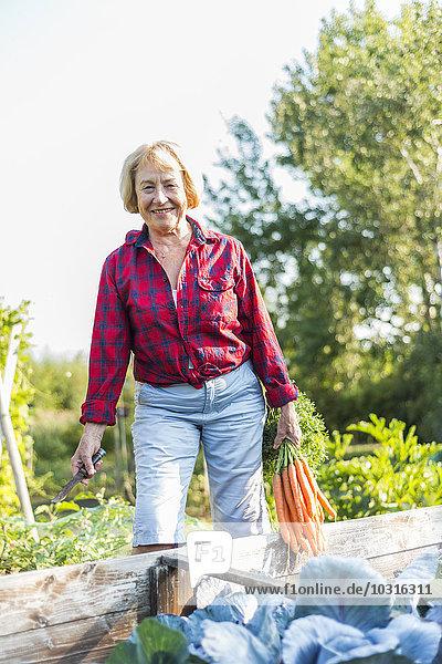 Lächelnde Seniorin im Gemüsebeet
