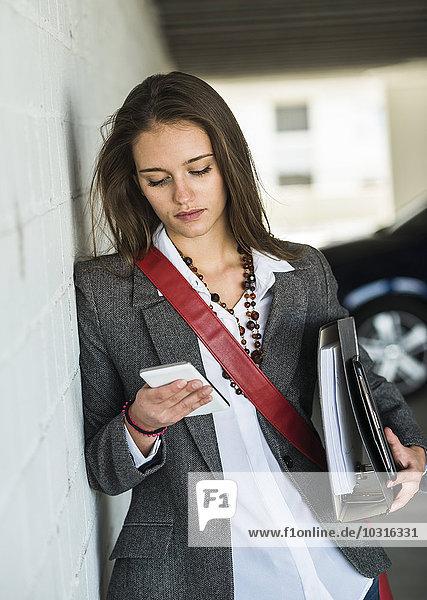 Junge Frau hält Mappe mit Blick auf Handy