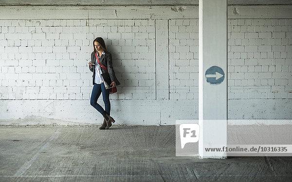 Junge Frau in einem Parkhaus mit Mappe und Blick auf Handy