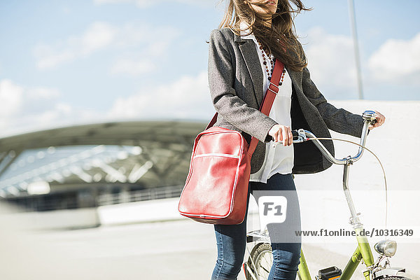 Junge Frau schiebt Fahrrad