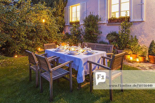 Herbstlich gedeckter Tisch im Garten am Abend