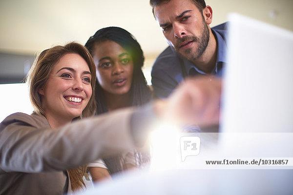 Drei Geschäftsleute beobachten am Laptop