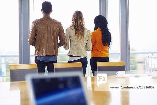 Drei kreative Menschen stehen nebeneinander in einem Konferenzraum mit Blick aus dem Fenster.