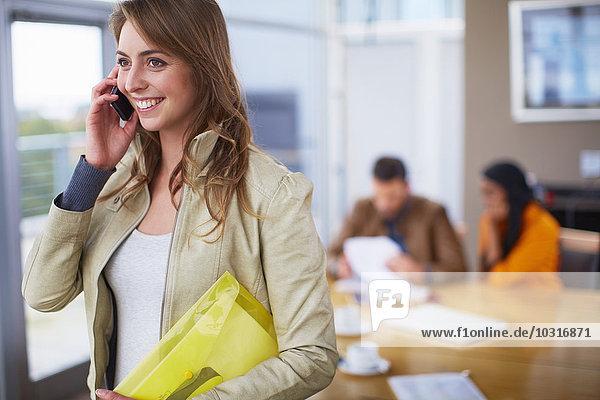 Portrait der Geschäftsfrau beim Telefonieren mit dem Smartphone im Büro