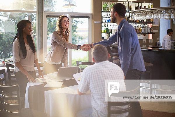 Zwei Personen begrüßen sich bei einem Geschäftstreffen in einem Restaurant.