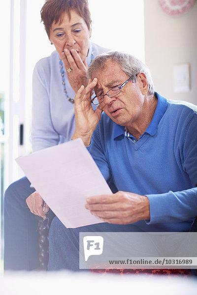 Schockiertes Seniorenpaar beim Lesen des Dokuments zu Hause