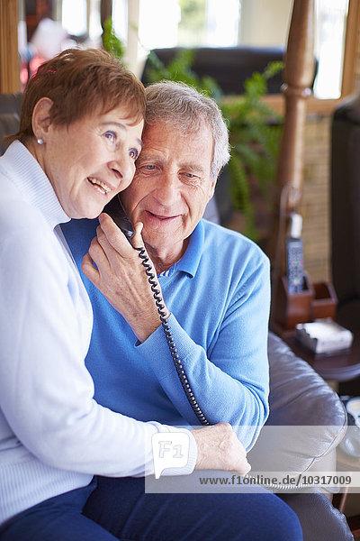 Glückliches Ehepaar  das sich zu Hause einen Telefonhörer teilt.