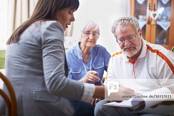 Frau erklärt dem älteren Ehepaar das Dokument