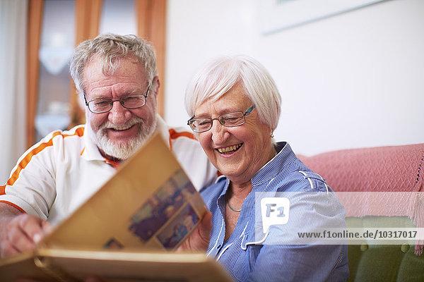 Seniorenpaar zu Hause beim Betrachten des Fotoalbums