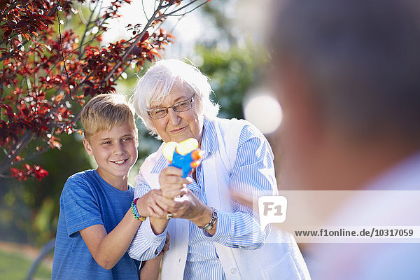 Grandson and grandmother splashing at grandfather with water gun