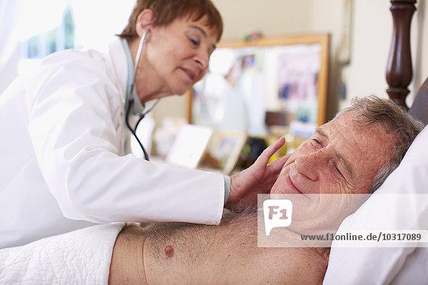 Arzt untersucht älteren Mann zu Hause
