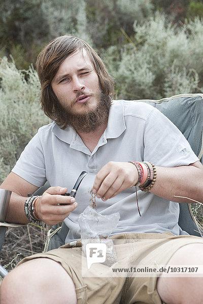 Young man preparing pipe