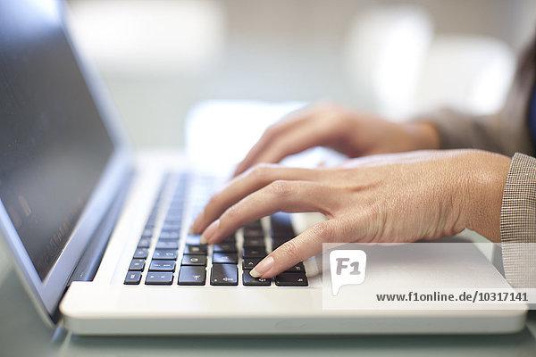 Hände der jungen Frau mit Laptop