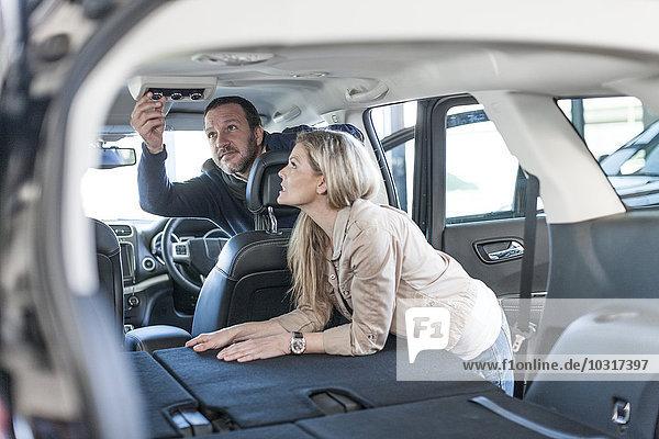 Paar untersucht neues Auto im Autohaus
