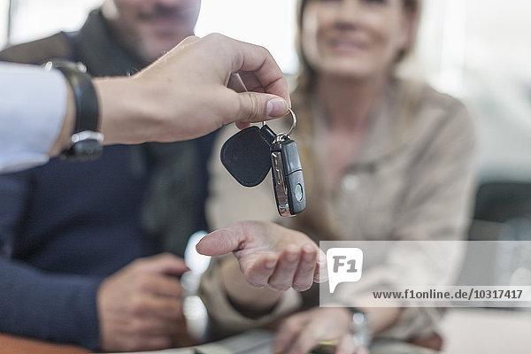 Autohändler übergibt Schlüssel an den Kunden