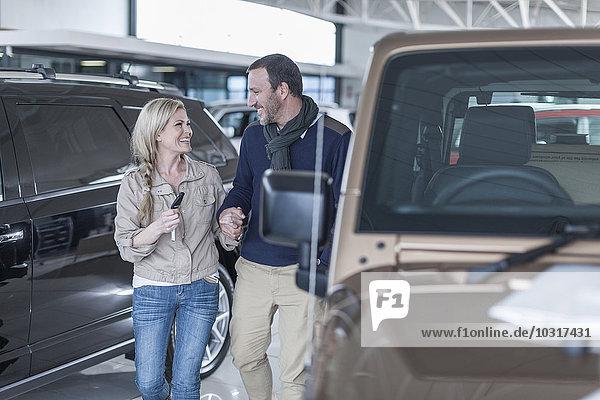 Glückliches Paar im Autohaus Hand in Hand am Neuwagen