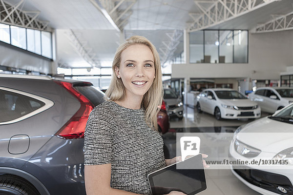 Lächelnde junge Frau im Autohaus