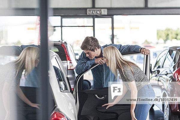 Junges Ehepaar untersucht neues Auto im Autohaus