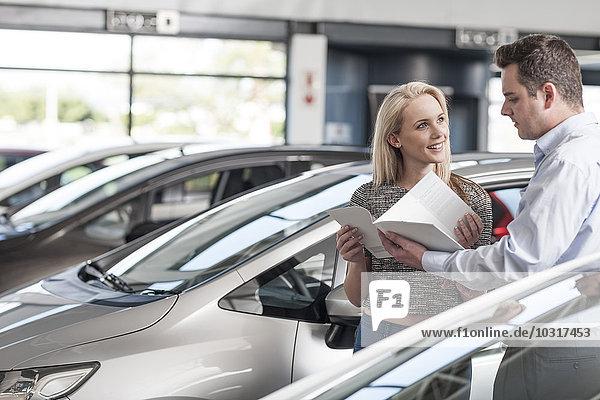 Autohändlerin erklärt der jungen Frau das neue Auto