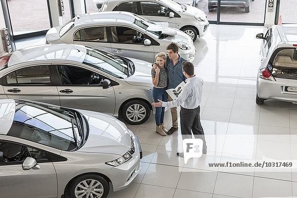 Autohändler zeigt neues Auto dem jungen Paar im Showroom