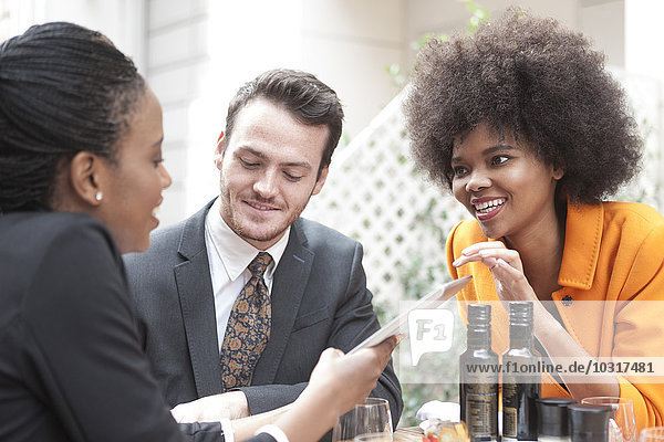 Drei Kollegen mit digitalem Tablett im Außenrestaurant Drei Kollegen mit digitalem Tablett im Außenrestaurant