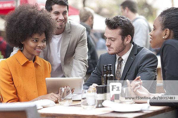 Kollegen mit digitalem Tablett im Außenrestaurant