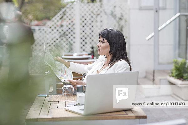Frau im Outdoor-Café mit Zeitung und Laptop Frau im Outdoor-Café mit Zeitung und Laptop