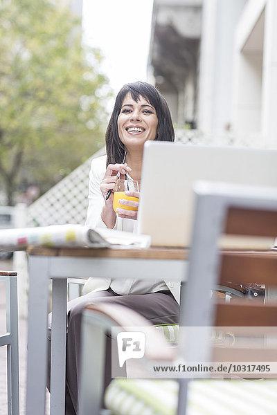 Lächelnde Frau im Outdoor-Café mit Getränk und Laptop Lächelnde Frau im Outdoor-Café mit Getränk und Laptop