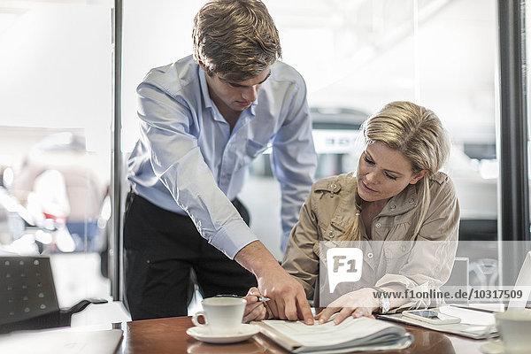 Woman signing sales contract at car dealership