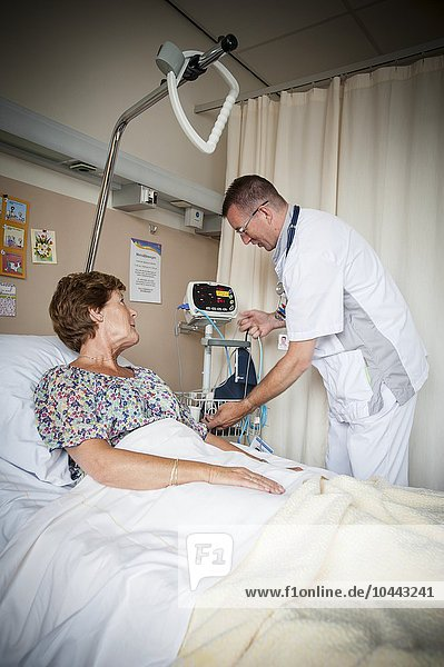 MODEL RELEASED. Blood pressure measurement. Nurse preparing to measure a patient's blood pressure. Blood pressure measurement