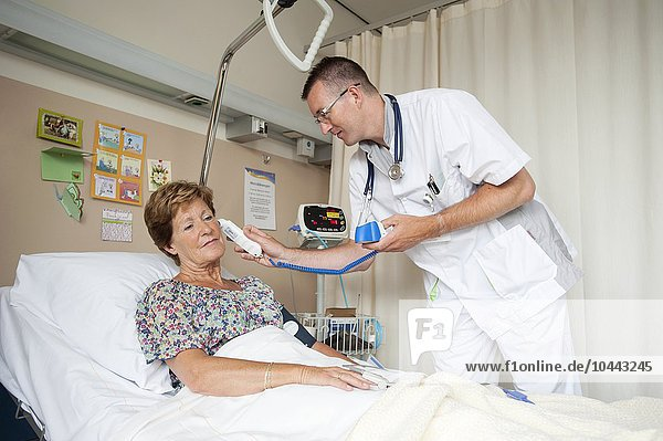 MODEL RELEASED. Taking temperature. Nurse taking a patients temperature with a digital thermometer. Taking temperature