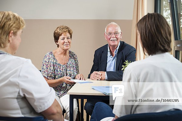 MODEL RELEASED. Hospital consultation. Care team meeting with a patient and her partner. Hospital consultation