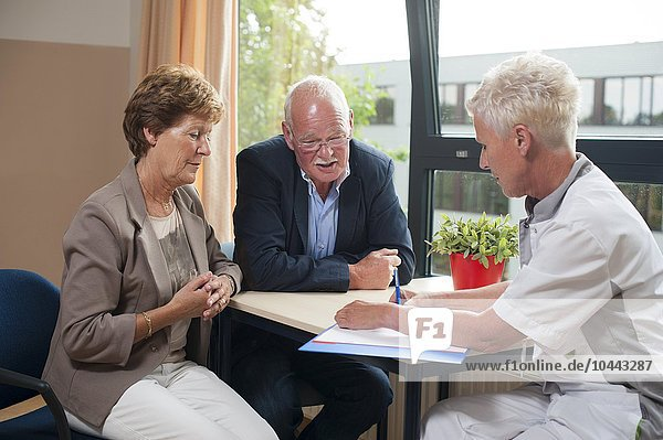 MODEL RELEASED. Hospital consultation. Nurse meeting with a patient and her partner. Hospital consultation