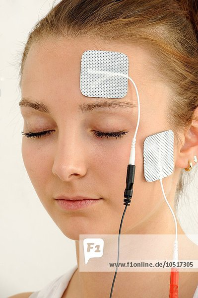 Electrodes in pads attached to a woman  transcutaneous electronic nerve stimulation