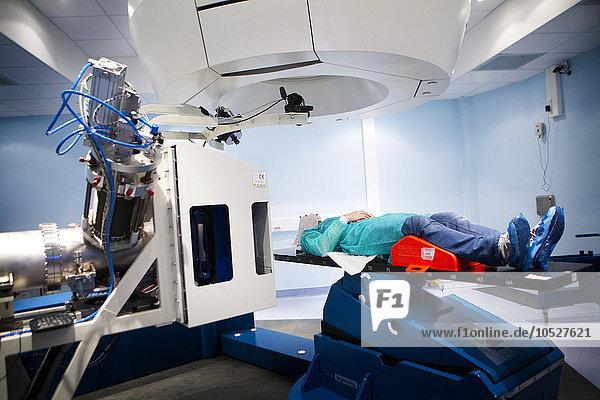Reportage im Nationalen Onkologie-Partikel-Therapiezentrum in Mailand  Italien (Das CNAO - Centro Nazionale di Adroterapia Oncologica). Partikeltherapie ist eine hochmoderne Technik zur Behandlung von Krebs. Es besteht aus der Verwendung von Hadronen  Protonen (Protonentherapie) und Cabon-Ionen (Kohlenstoff-Ionen-Behandlung)  um Tumore zu bestrahlen. Es hat zwei therapeutische Zwecke  eine hohe ballistische Genauigkeit  die es ermöglicht  dass gesundes Gewebe um den Tumor herum verschont wird  und eine größere Effizienz bei der Behandlung bestimmter Krebsarten. Die CNAO ist das einzige Zentrum für die Carbon-Ionen-Behandlungstechnik in Europa. Der Patient trägt eine Maske  die Bewegung während der Behandlung verhindert.
